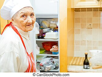 Food ingedients - Elderly lady in the kitchen at home ...