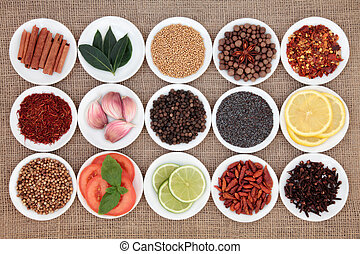 Large spice, herb and food ingredient selection in white porcelain bowls over hessian background.