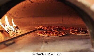 peel placing pizza baking in oven at pizzeria