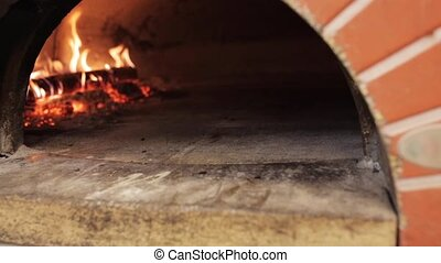 peel placing pizza baking into oven at pizzeria