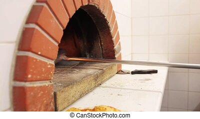 peel taking pizza out of oven at pizzeria
