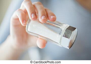 close up of hand holding white salt cellar - food,...