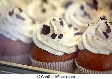 close up of cupcakes or muffins with frosting - food,...