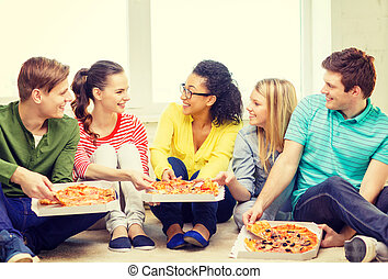 five smiling teenagers eating pizza at home - food, leisure ...