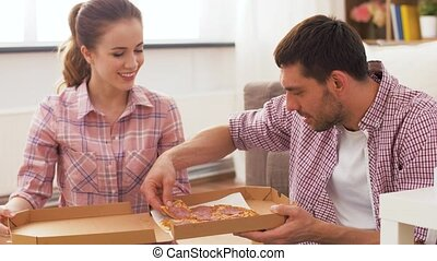 couple eating takeaway pizza at home - food, leisure and...
