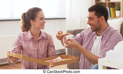 food, leisure and people concept - happy couple eating takeaway pizza at home