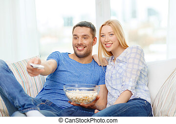 smiling couple with popcorn watching movie at home