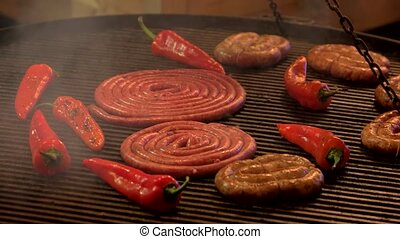 Food on grill. Hand with tongs, sausages.