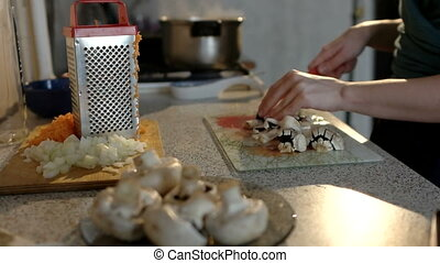 Food on kitchen table, girl is cutting mushrooms while cooking.