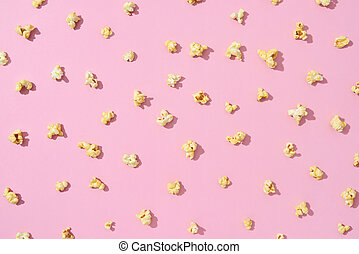 Food pattern from delicious popcorn on a light pink background.