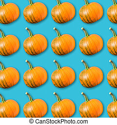 Food pattern with arrangement of orange pumpkins on turquoise background