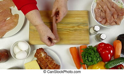 Women's hands tenderizing chicken breast. Shoot from above