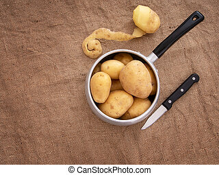 Food preparation, peeling potatoes in a rustic setting still life with saucepan, knife, hessian aka jute. Overhead view.
