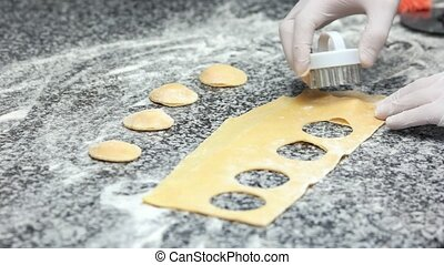 Food preparation, ravioli cutter. Hands making food close...