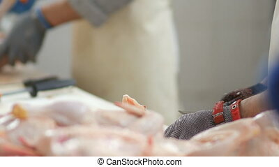 Food processing plant, chicken meat. Workers hands cut meat...