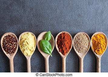 Food seasoning border - Herbs and spices in wooden spoons...