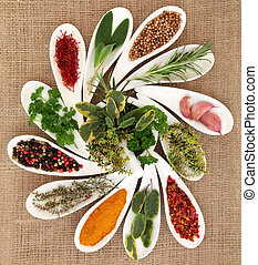 Spice and fresh herb selection in porcelain dishes and mortar with pestle over hessian background.