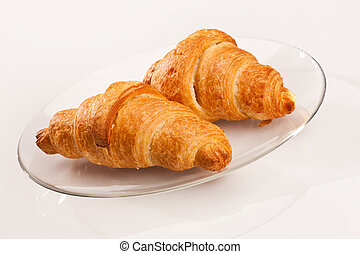 croissant - food series: two tasty fresh croissant on glassy...