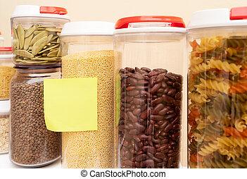 Food storage - raw food ingredients inside transparent jars, copy space on paper sticker