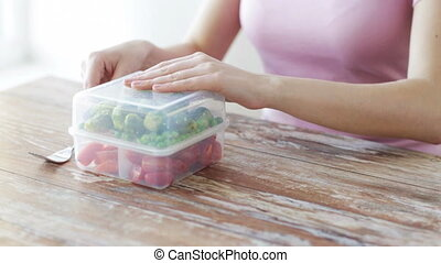 close up of woman eating vegetables from container