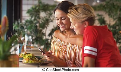 female friends with smartphone at restaurant - food,...