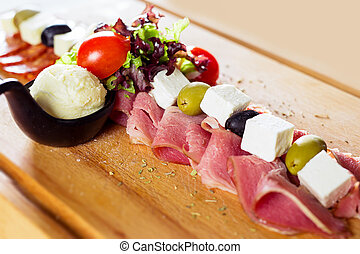 Food tray with delicious salami, pieces of sliced ham, sausage, tomatoes, salad and vegetable