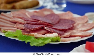 Food tray with delicious salami, pieces of sliced ham,...