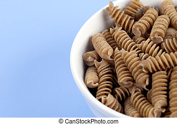 A bowl of wholewheat Rotini Pasta on a fresh, light-blue background.