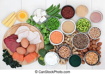Food with high protein content with legumes, meat, fish, dairy, nuts, tofu, seeds, grains and supplement powders. Foods high in dietary fibre, antioxidants and vitamins. Top view on white wood.