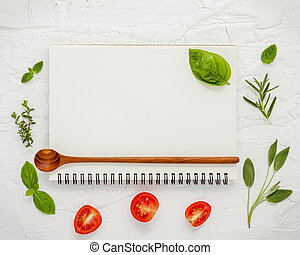 Foods background and Food menu design . Various herbs ingredients sweet basil, sage ,lemon thyme ,rosemary, cherry tomatoes sliced setup with white notebook on white shabby table.