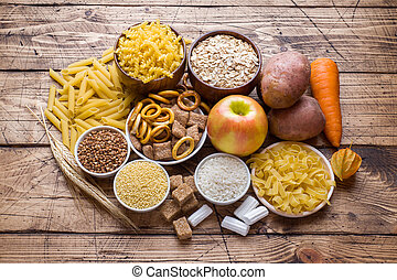 Foods high in carbohydrate on rustic wooden background.