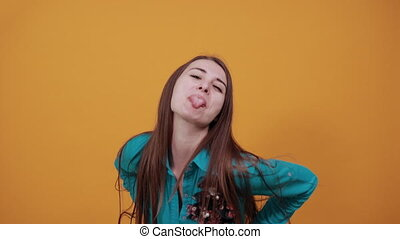 Fooling around outside, sticks out tongue as sign of disobedience, protest and disrespect. Human emotions, reactions, feelings, attitude, having fun, grimacing healthy oral cavity. Attractive woman