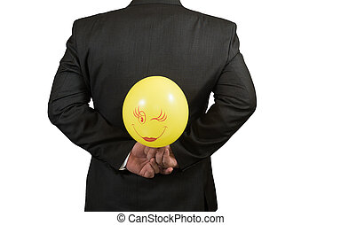 Fool's day is businessman with a balloon behind his back, isolated