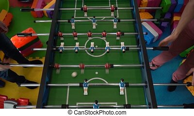 Foosball. Hands of a man playing table football.