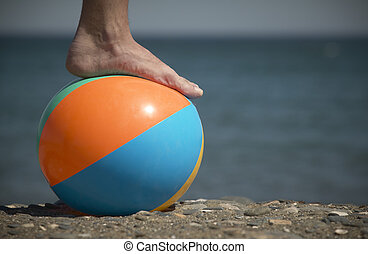 Foot and ball on the beach with the sea out of focus