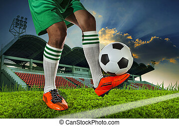 foot ball player holding foot ball on leg ankle on soccer sport field agianst stadium and dusky sky use for soccer footbal teaml competition