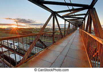 Foot bridge over railway at sunset