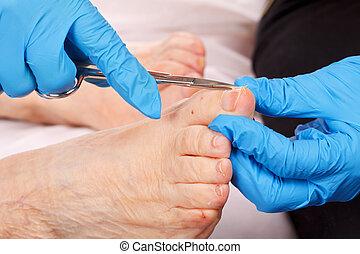 Foot care - doctor hand examining an elderly patient's foot