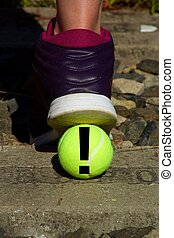 Foot in a sports shoe and a tennis ball with black exclamation mark.