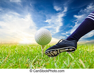 foot kicking golf ball on tee