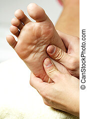 Foot massage - A masseuse massaging the feet of a woman