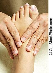 Foot massage - A masseuse massaging the foot of a woman