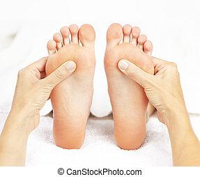 Foot massage - Female hands giving massage to soft bare feet