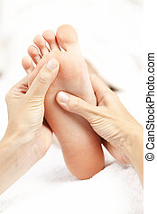 Female hands giving massage to soft bare foot
