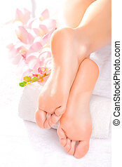 Foot massage in the spa salon with orchid