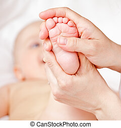 Foot massage - Masseur massaging little baby's foot, shallow...