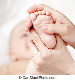 Foot massage - Mother massaging her child\'s foot, shallow...