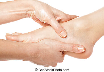 Foot massage - woman hands giving a foot massage on white...