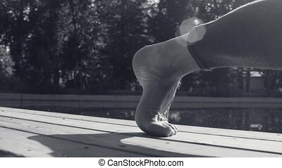 Foot of a woman doing yoga exercises in the park - Close up...