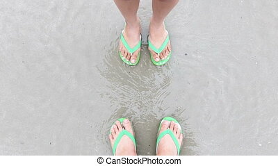 Foot of boy and girl or man and woman soak in water at sea beach and sand.
